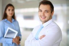 Χαμογελώντας επιχειρηματίας στην αρχή με τους συναδέλφους στο υπόβαθρο Στοκ εικόνες με δικαίωμα ελεύθερης χρήσης