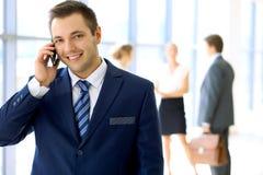 Χαμογελώντας επιχειρηματίας στην αρχή με τους συναδέλφους στο υπόβαθρο και τη χρησιμοποίηση κινητά Στοκ φωτογραφία με δικαίωμα ελεύθερης χρήσης