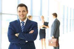 Χαμογελώντας επιχειρηματίας στην αρχή με τους συναδέλφους στο υπόβαθρο Στοκ Φωτογραφίες