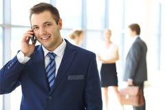 Χαμογελώντας επιχειρηματίας στην αρχή με τους συναδέλφους στο υπόβαθρο Στοκ Εικόνες