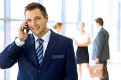 Χαμογελώντας επιχειρηματίας στην αρχή με τους συναδέλφους στο υπόβαθρο και τη χρησιμοποίηση κινητά Στοκ Εικόνα