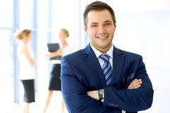 Χαμογελώντας επιχειρηματίας στην αρχή με τους συναδέλφους στο υπόβαθρο Στοκ φωτογραφία με δικαίωμα ελεύθερης χρήσης