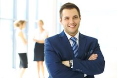 Χαμογελώντας επιχειρηματίας στην αρχή με τους συναδέλφους στο υπόβαθρο Στοκ Εικόνα