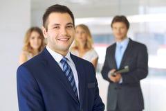 Χαμογελώντας επιχειρηματίας στην αρχή με τους συναδέλφους στο υπόβαθρο Στοκ εικόνα με δικαίωμα ελεύθερης χρήσης