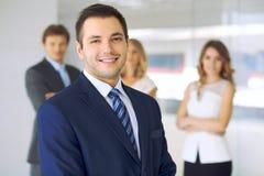 Χαμογελώντας επιχειρηματίας στην αρχή με τους συναδέλφους στο υπόβαθρο Στοκ Φωτογραφία