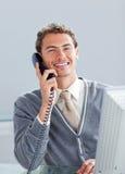 Χαμογελώντας επιχειρηματίας στο τηλέφωνο στο γραφείο του Στοκ Φωτογραφίες