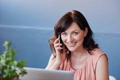 Χαμογελώντας επιχειρηματίας χρησιμοποιώντας ένα lap-top και μιλώντας στο κινητό τηλέφωνο της Στοκ Φωτογραφίες