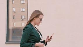 Χαμογελώντας επιχειρηματίας eyeglasses που περπατούν και που χρησιμοποιούν την ψηφιακή συσκευή υπαίθρια φιλμ μικρού μήκους