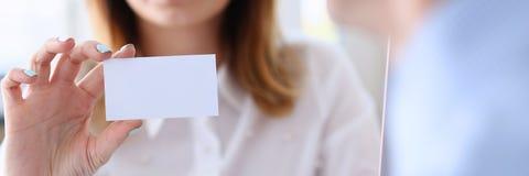 Χαμογελώντας επιχειρησιακή γυναίκα στη διαθέσιμη κενή τηλεπικοινωνιακή κάρτα λαβής κοστουμιών Στοκ Φωτογραφία