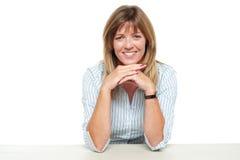 Χαμογελώντας επιχειρησιακή κυρία που κάθεται μη απασχόλησης στην αρχή Στοκ εικόνα με δικαίωμα ελεύθερης χρήσης