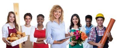 Χαμογελώντας επιχειρησιακός εκπαιδευόμενος θηλυκών με την ομάδα άλλων διεθνών μαθητευόμενων στοκ εικόνες