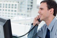 Χαμογελώντας εργαζόμενος γραφείων στο τηλέφωνο Στοκ εικόνες με δικαίωμα ελεύθερης χρήσης