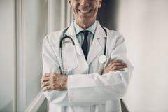 Χαμογελώντας εργαζόμενος ιατρικής με τα διασχισμένα όπλα στοκ εικόνες