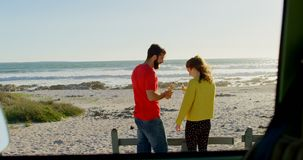 Χαμογελώντας ευτυχές νέο ζεύγος που έχει την μπύρα στην παραλία 4k απόθεμα βίντεο