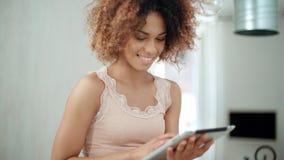 Χαμογελώντας ευτυχής αμερικανική γυναίκα afro που χρησιμοποιεί την ταμπλέτα PC στο σπίτι Στοκ εικόνες με δικαίωμα ελεύθερης χρήσης