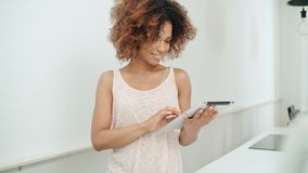 Χαμογελώντας ευτυχής αμερικανική γυναίκα afro που χρησιμοποιεί την ταμπλέτα PC στο σπίτι Στοκ φωτογραφία με δικαίωμα ελεύθερης χρήσης