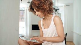 Χαμογελώντας ευτυχής αμερικανική γυναίκα afro που χρησιμοποιεί την ταμπλέτα PC στο σπίτι Στοκ Εικόνες