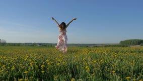 Χαμογελώντας ευτυχής γυναίκα που περπατά σε έναν ανθίζοντας κίτρινο τομέα σε ένα φόρεμα που γυρίζει γύρω απόθεμα βίντεο