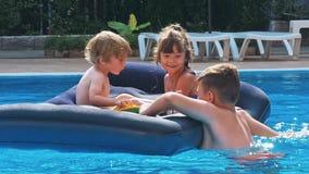 Χαμογελώντας, ευτυχή παιδιά σε ένα επιπλέον σώμα σε μια πισίνα απόθεμα βίντεο