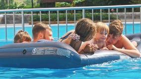 Χαμογελώντας, ευτυχή παιδιά σε ένα επιπλέον σώμα σε μια πισίνα φιλμ μικρού μήκους
