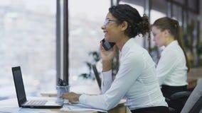 Χαμογελώντας εύθυμη γυναίκα εργαζόμενος που μιλά στο smartphone με τον πελάτη, ομαδική εργασία απόθεμα βίντεο