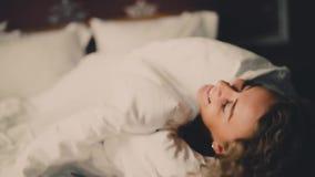 Χαμογελώντας εύθυμη γυναίκα που κρυφοκοιτάζει έξω από κάτω από το κάλυμμα στο κρεβάτι στο σπίτι και τη κάμερα φιλήματος φιλμ μικρού μήκους