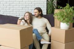 Χαμογελώντας ζεύγος με τα κιβώτια που κάθεται στον καναπέ που αγκαλιάζει, κινούμενη ημέρα στοκ φωτογραφία