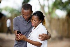 Χαμογελώντας ζεύγος με το κινητό τηλέφωνο έξω στοκ εικόνες με δικαίωμα ελεύθερης χρήσης