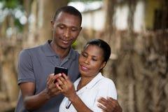 Χαμογελώντας ζεύγος με το κινητό τηλέφωνο έξω στοκ εικόνες