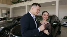 Χαμογελώντας ζεύγος που αγκαλιάζει και που κρατά το νέο κλειδί τους στη νέα αίθουσα εκθέσεως αυτοκινήτων απόθεμα βίντεο