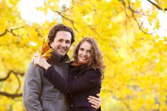 Χαμογελώντας ζεύγος που αγκαλιάζει στο πάρκο φθινοπώρου στοκ φωτογραφία με δικαίωμα ελεύθερης χρήσης