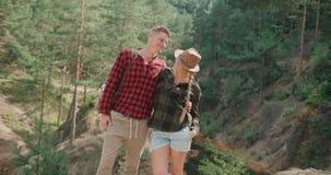 Χαμογελώντας ζεύγος που εξετάζει τη κάμερα χαλαρώνοντας στα ξύλα φιλμ μικρού μήκους