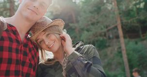 Χαμογελώντας ζεύγος που εξετάζει τη κάμερα χαλαρώνοντας στα ξύλα απόθεμα βίντεο