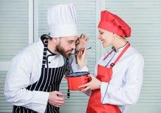 Μυστικό συστατικό από τη συνταγή μάγειρας ομοιόμορφος ζεύγος ερωτευμένο με τα τέλεια τρόφιμα αρχιμάγειρας ανδρών και γυναικών Προ στοκ εικόνες με δικαίωμα ελεύθερης χρήσης