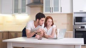 Χαμογελώντας ζεύγος που στέκεται εξετάζοντας το lap-top στην κουζίνα φιλμ μικρού μήκους
