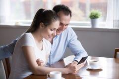 Χαμογελώντας ζεύγος που ψωνίζει on-line στο smartphone που έχει το πρωί coff στοκ εικόνα με δικαίωμα ελεύθερης χρήσης