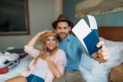 χαμογελώντας ζεύγος στο δωμάτιο ξενοδοχείου με τα διαβατήρια με τα εισιτήρια Στοκ φωτογραφία με δικαίωμα ελεύθερης χρήσης