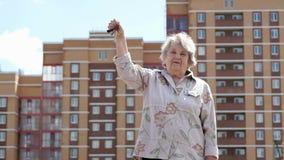 Χαμογελώντας ηλικιωμένη γυναίκα που αυξάνει το χέρι επάνω με τα κλειδιά απόθεμα βίντεο