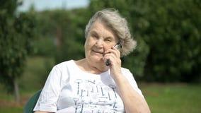 Χαμογελώντας ηλικιωμένη γυναίκα που μιλά χρησιμοποιώντας ένα έξυπνο τηλέφωνο φιλμ μικρού μήκους