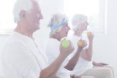 Χαμογελώντας ηλικιωμένοι άνθρωποι που ανυψώνουν τους αλτήρες στοκ εικόνες