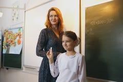 Χαμογελώντας ηλικιωμένος δάσκαλος κοντά στον πίνακα κιμωλίας που ρωτά το σπουδαστή Στοκ Εικόνες