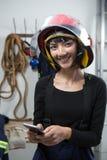 Χαμογελώντας θηλυκός αρχιτέκτονας που χρησιμοποιεί το κινητό τηλέφωνο Στοκ Εικόνες