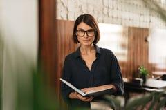 Χαμογελώντας θηλυκός διευθυντής eyeglasses με τα έγγραφα στα χέρια Στοκ Φωτογραφίες