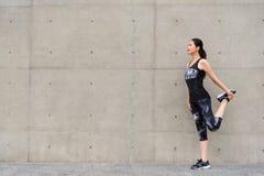 Χαμογελώντας θηλυκός δρομέας που κάνει τα πόδια τεντώματος Στοκ Εικόνες