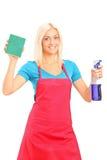 Χαμογελώντας θηλυκός καθαριστής που κρατά ένα σφουγγάρι και έναν ψεκασμό στοκ εικόνες