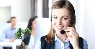 Χαμογελώντας θηλυκός κεντρικός χειριστής κλήσης που κάνει την εργασία της με μια κάσκα εξετάζοντας τη κάμερα Στοκ Φωτογραφία