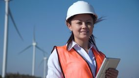 Χαμογελώντας θηλυκός μηχανικός που στέκεται ενάντια στο αιολικό πάρκο φιλμ μικρού μήκους
