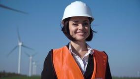 Χαμογελώντας θηλυκός μηχανικός που στέκεται ενάντια στο αιολικό πάρκο απόθεμα βίντεο