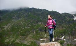 Χαμογελώντας θηλυκός ορειβάτης που φθάνει στην κορυφή βράχου με τα όμορφα πράσινα βουνά στη Ρουμανία στοκ εικόνες