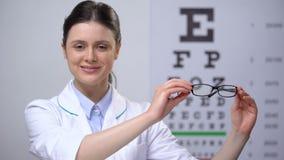 Χαμογελώντας θηλυκός οφθαλμολόγος που συστήνει eyeglasses, διόρθωση όρασης απόθεμα βίντεο